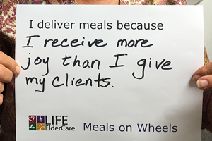 Sign written by volunteer: I deliver meals because I receive more joy than I give my clients