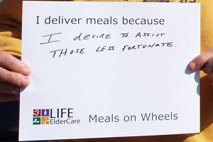 Sign written by volunteer: I deliver meals because I desire to assist those less fortunate